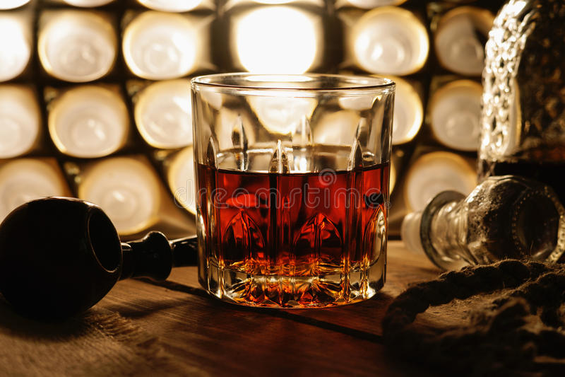 Glass of whiskey, tobacco pipe and rope stock photo