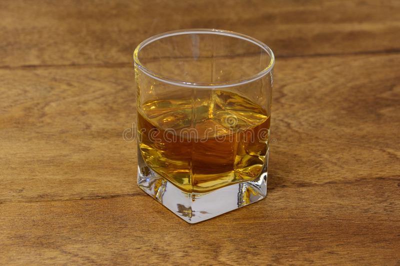 A glass of whiskey on a wooden table top stock photos