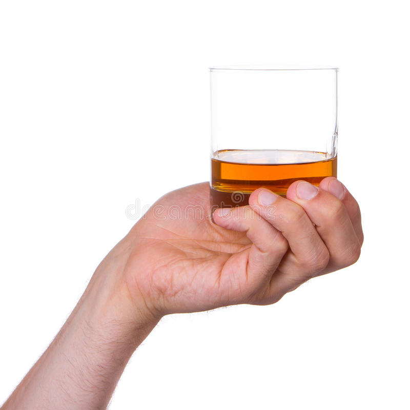 Glass of whisky in hand. Isolated on a white royalty free stock images