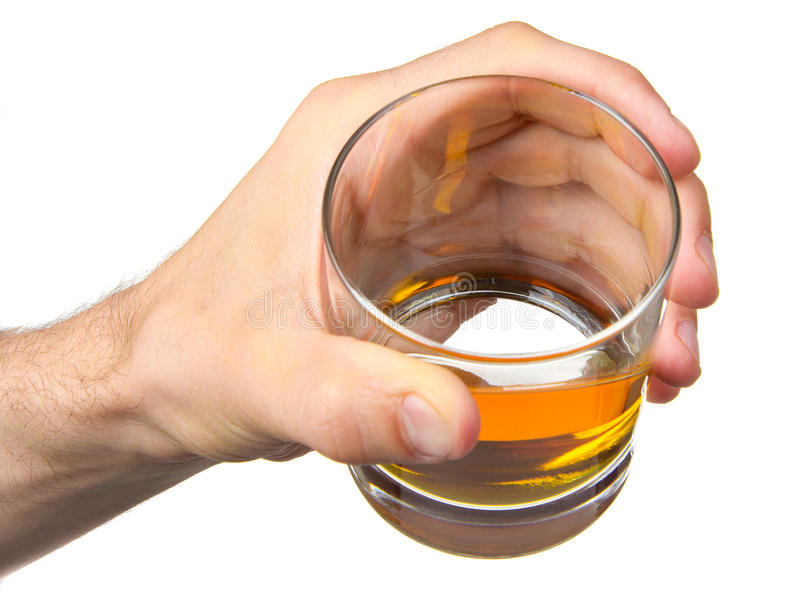Glass of whisky in hand. Isolated on a white royalty free stock image