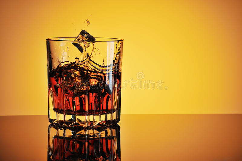 Glass of whisky with ice and splash. Glass of whisky with ice against yellow background stock photos