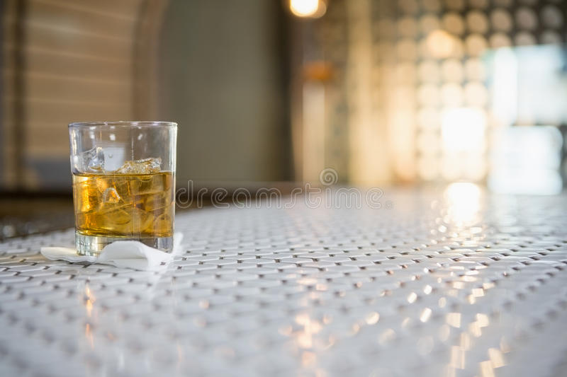 Glass of whisky with ice cube on bar counter stock photos