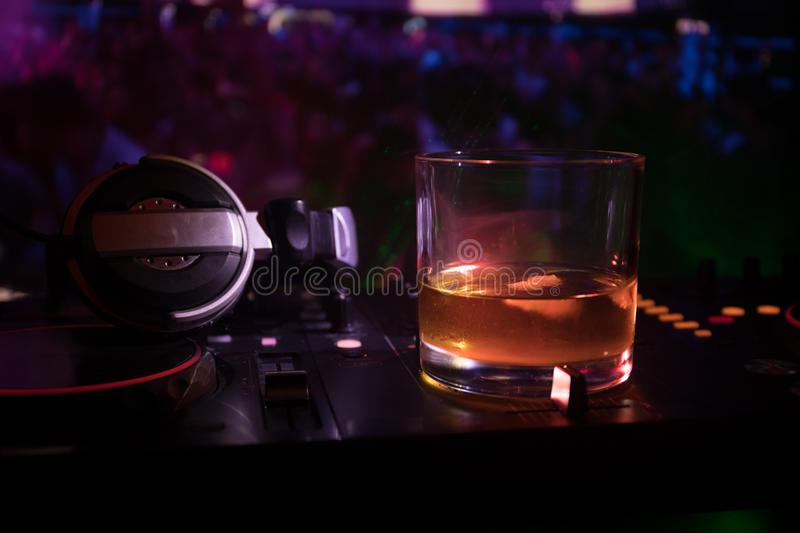 Glass with whisky with ice cube inside on dj controller at nightclub. Dj Console with club drink at music party in nightclub with royalty free stock photo