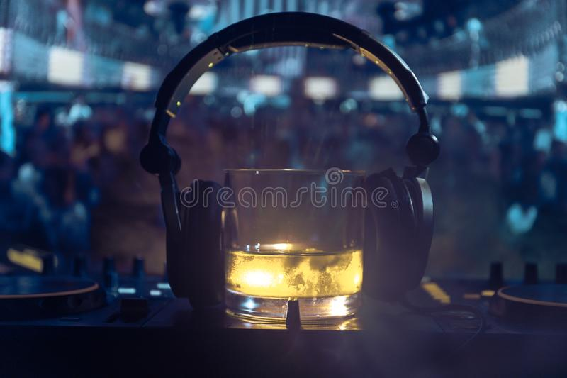 Glass with whisky with ice cube inside on dj controller at nightclub. Dj Console with club drink at music party in nightclub with. Glass with whisky with ice royalty free stock images