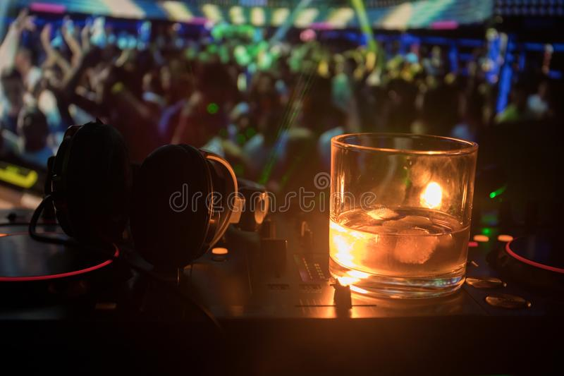 Glass with whisky with ice cube inside on dj controller at nightclub. Dj Console with club drink at music party in nightclub with royalty free stock images