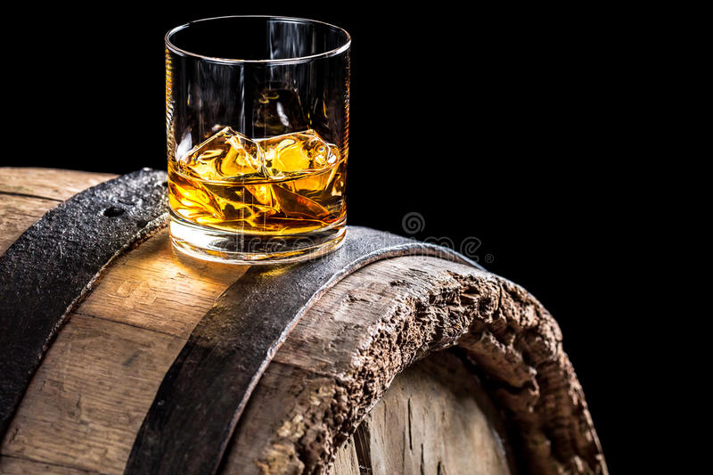 Glass of whisky with ice on old oak barrel. Isolated on a black background royalty free stock image