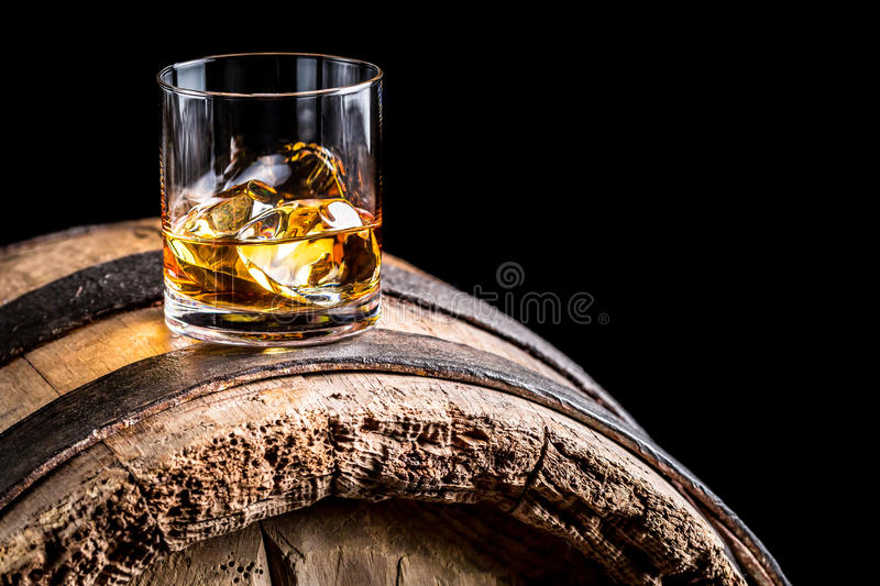 Glass of whisky with ice on old wooden barrel. Isolated on a black background royalty free stock photo