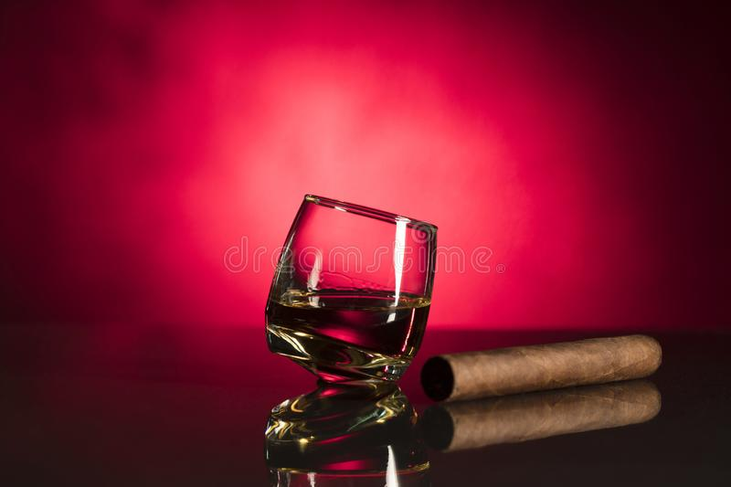 Glass with whisky isolated over red background stock images