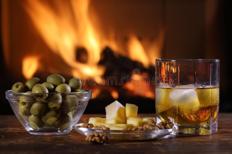 A glass of whisky and plate with cheese, olives and nuts royalty free stock images