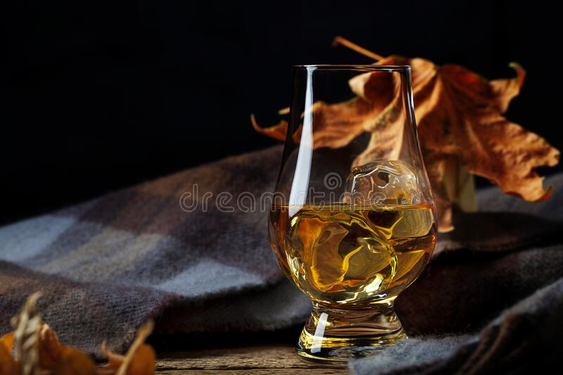 Glass with Whisky and Scottish Plaid Scarf royalty free stock photos