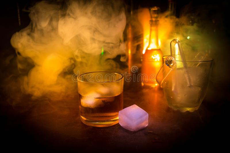 Glass of whisky on wooden bar closeup with bottles blurred view on dark background with light and smoke. Single glass of whisky on royalty free stock photos