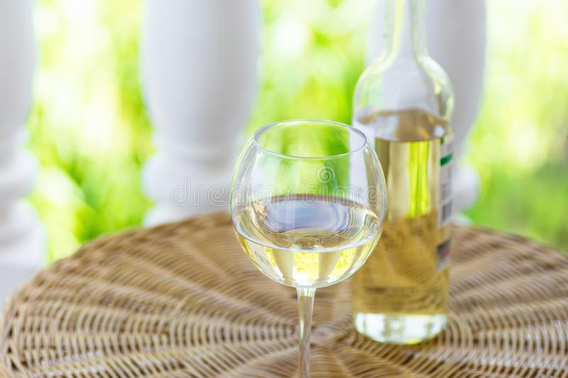 Glass of white dry wine and bottle on wicker table on garden terrace of villa or mansion. Authentic lifestyle image. royalty free stock photography