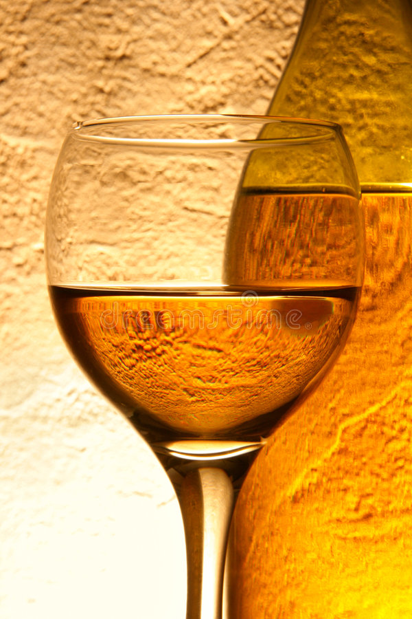 Glass of white wine and bottle royalty free stock photography