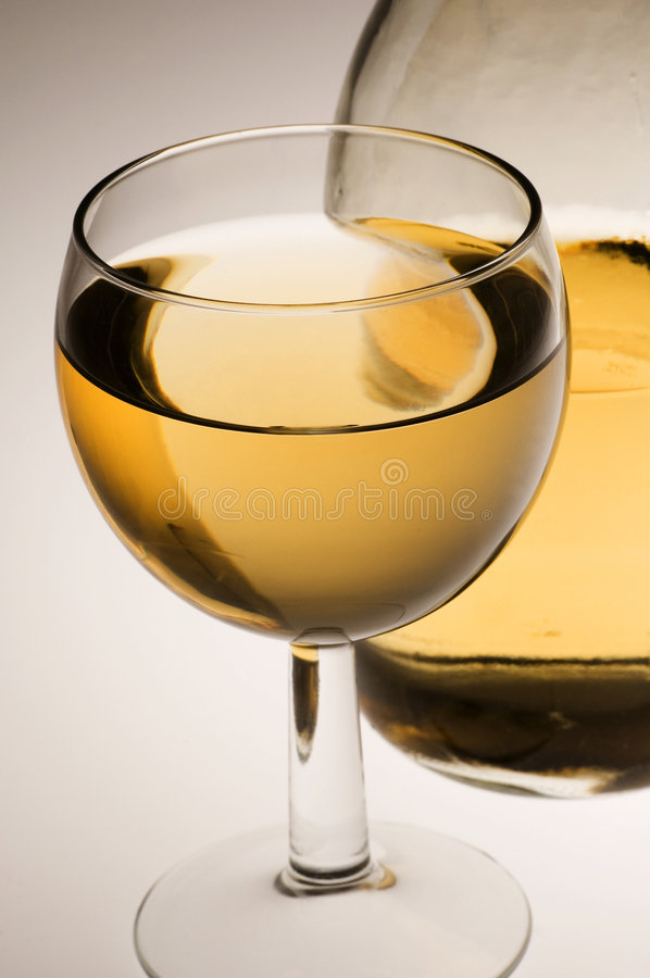 Glass of white wine and bottle stock image