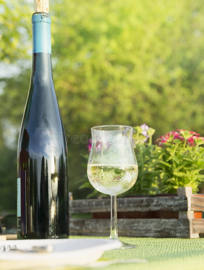 Glass of white wine with bottle in garden,picnic stock photography