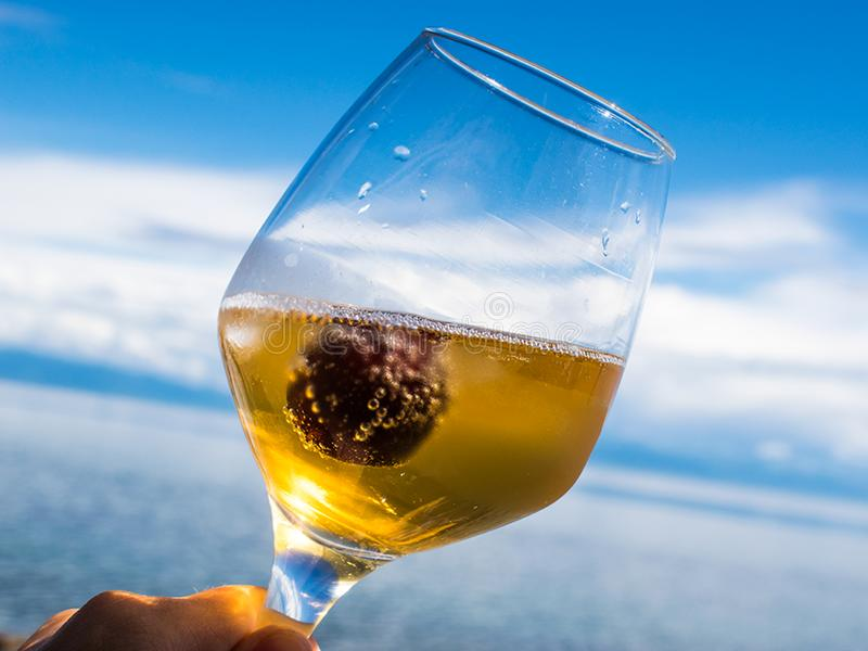 A glass of white wine with cherries against the blue sky. stock photos