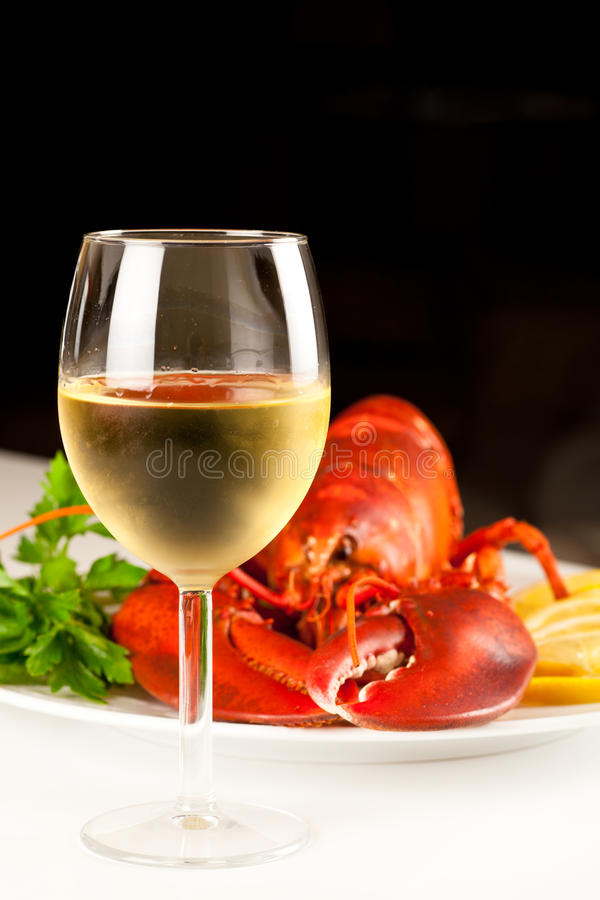 Glass of white wine with cooked lobster royalty free stock image