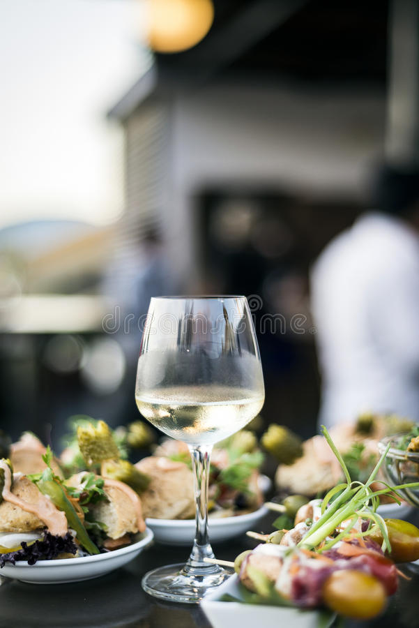 Glass of white wine with gourmet food tapa snacks outside. Glass of white wine with gourmet food tapa snacks in outdoors bar at sunset royalty free stock images