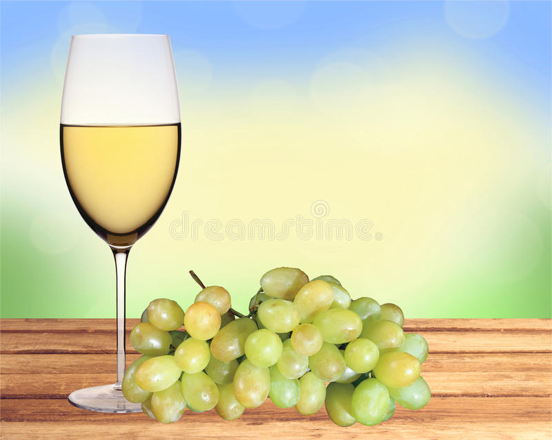 Glass of white wine and green grape on wooden table over nature royalty free stock image