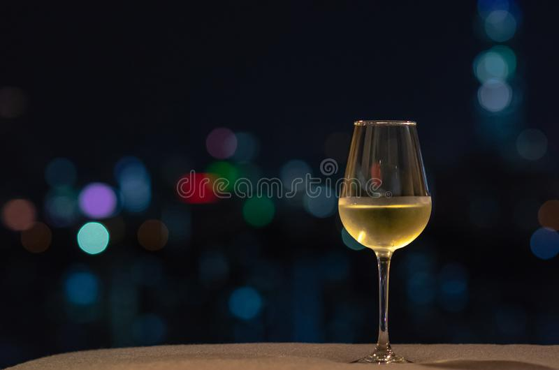 A glass with white wine puts on sofa with colorful bokeh light from city royalty free stock image
