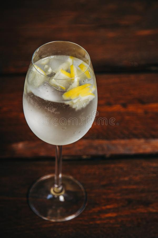A glass of white wine on a rustic wooden red background. rest, holiday, party. crystal glass closeup. copy space. top view stock photo