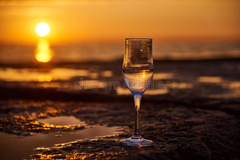 Glass of white wine and with sea and beautiful sunset at background, close-up. Summer evening relaxed mood concept stock photo