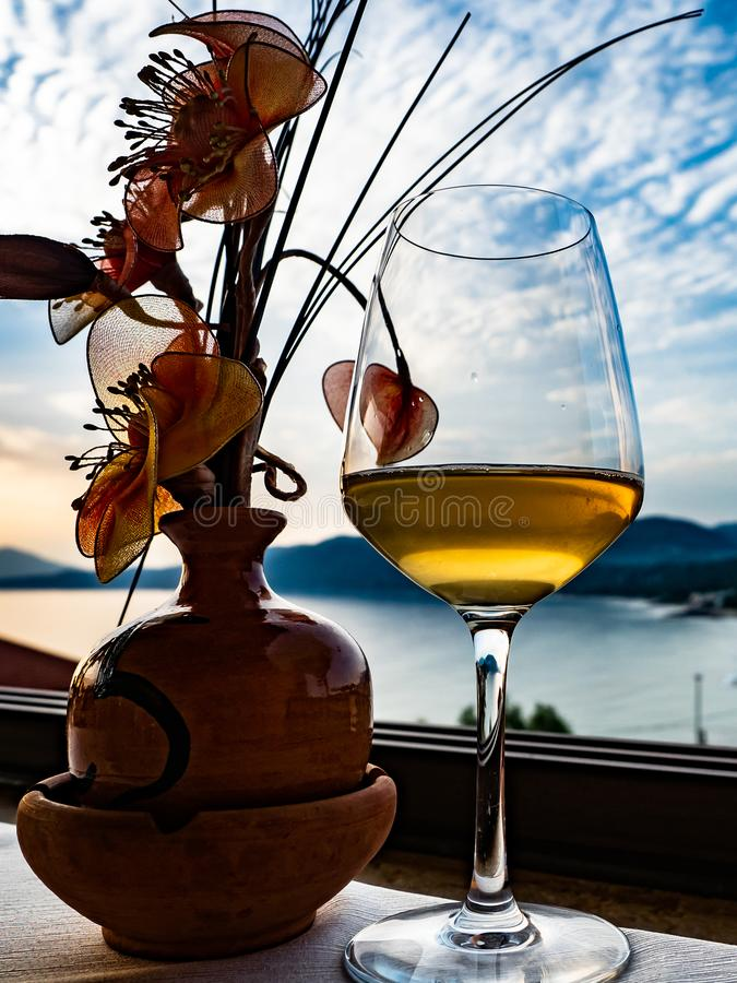 A glass of white wine with seascape at sunset royalty free stock image