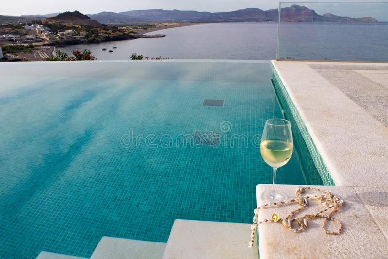 Glass of white wine with shell beads is located on the edge of the pool stairs.  royalty free stock photo