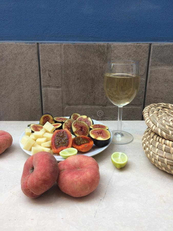 A glass of white wine and sliced fruit on a plate. royalty free stock image