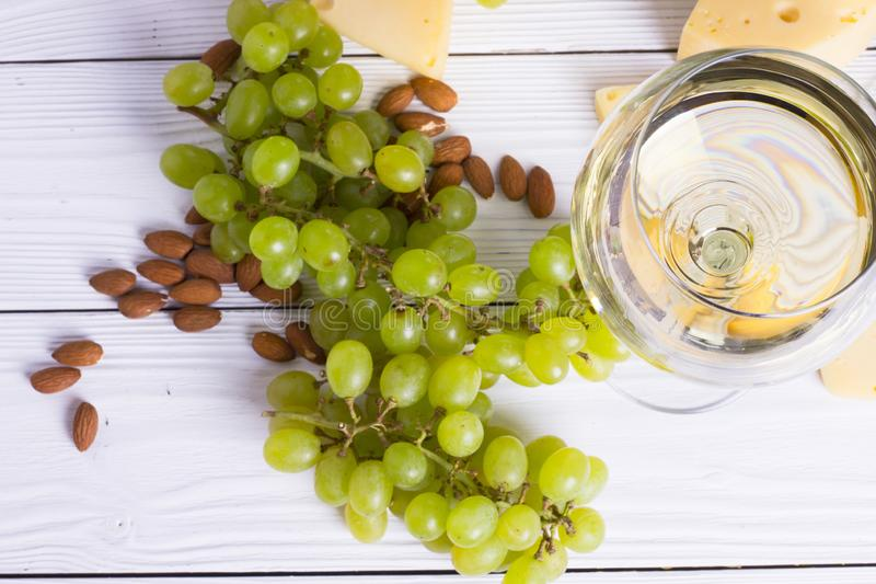 Glass of white wine with snacks - various types of cheese, figs, nuts, honey, grapes on a wooden boards background stock photo