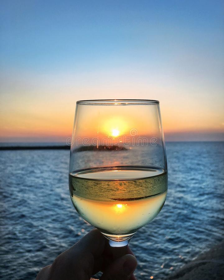 Glass of white wine at sunset by the sea royalty free stock photos