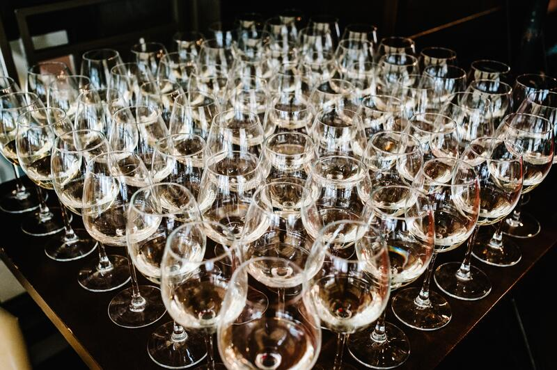 Glass of white wine on a table. Many glass wine in a row on bar counter. Shallow depth of field. Glasses with wine. Filled with stock image
