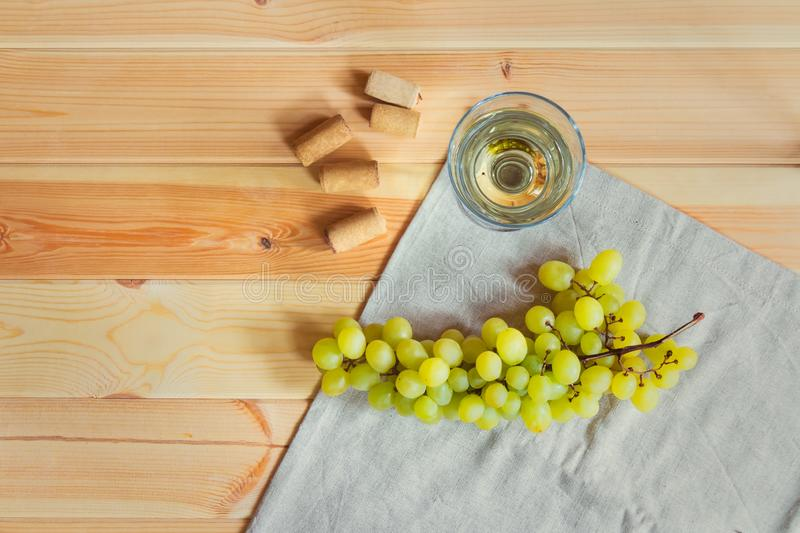 Glass of white wine, wine corks and grape branch on wooden table stock photos