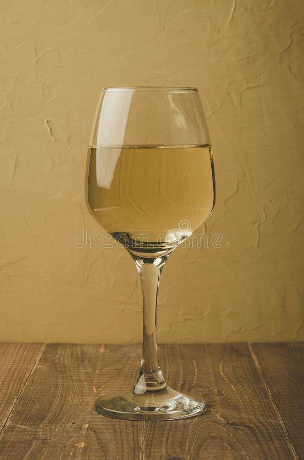 Glass of white wine on a wooden table/glass of white wine on a wooden table, selective focus. Background drink beverage alcohol vintage vine wineglass winery stock image