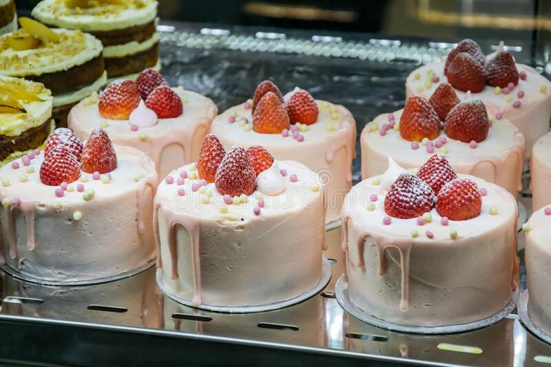 Glass window in a bakery shop with different types of cakes in a showcase. Delicious creamy fruit cakes decorated with fresh royalty free stock image