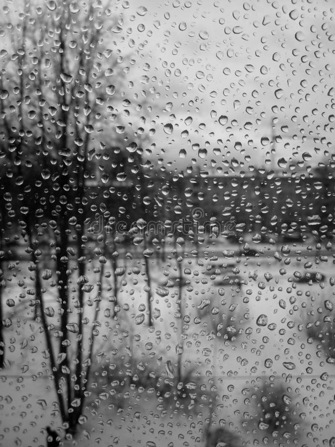 Raindrops on the glass, rain in the new year, rain with snow, wet weather, rainy weather, depression, gray sky royalty free stock photography