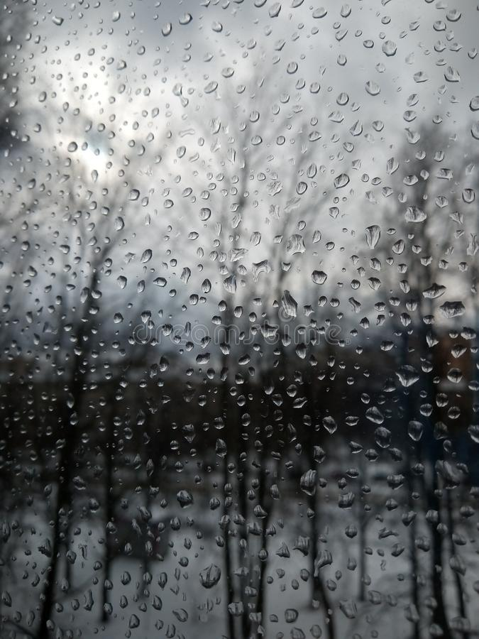 Raindrops on the glass, rain in the new year, rain with snow, wet weather, rainy weather, depression, gray sky royalty free stock photos