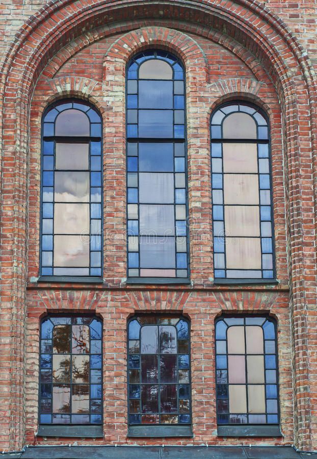 Glass window with stained-glass windows on the church building. View from the bottom royalty free stock images