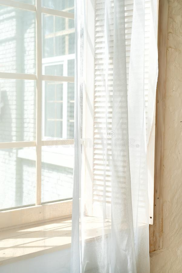 Glass windows with white curtains, morning sun light window. The shadow is projected on the wooden floor stock photography