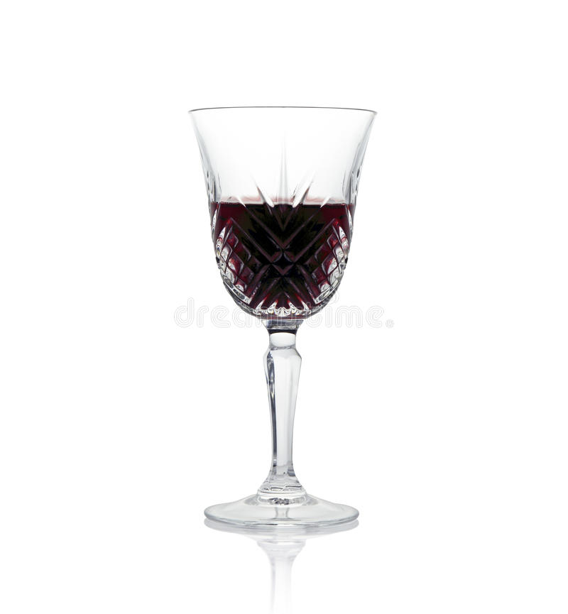 A glass of wine. A decorative crystal glass half filled with red wine with reflection, isolated against white royalty free stock photos