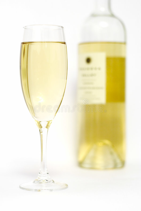 Glass of wine. A glass and a bottle of white wine stock photo