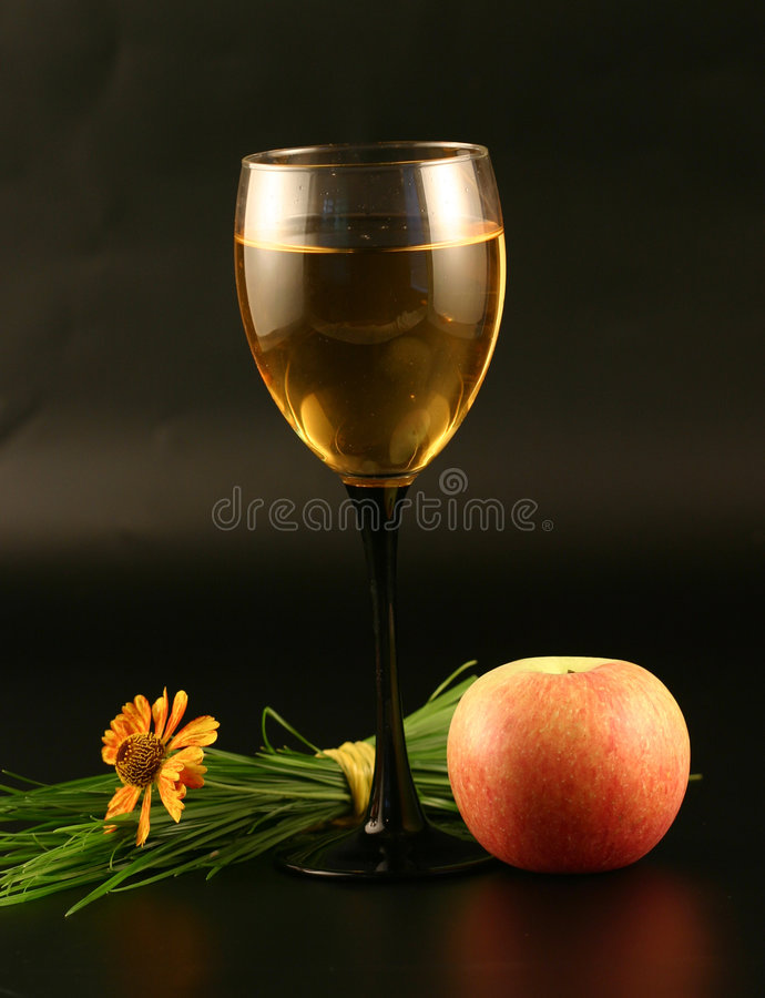 Glass of wine, apple and grass stock photography