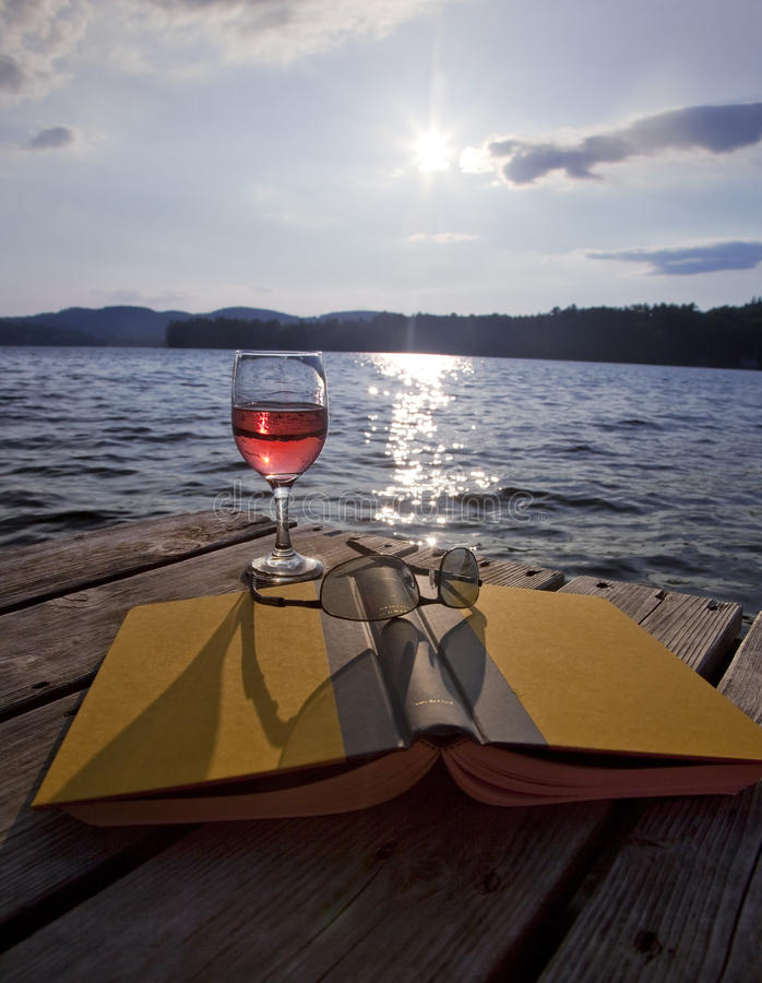 Glass of wine, book, and glasses at lake royalty free stock image