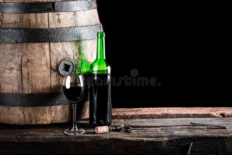 Glass of wine with bottle and old oak barrel. Isolated on a black background royalty free stock images