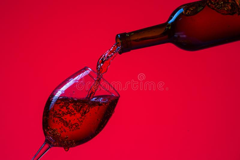 Glass of Wine and Bottle with Pouring Out Liquid. Against Red. Background royalty free stock photography