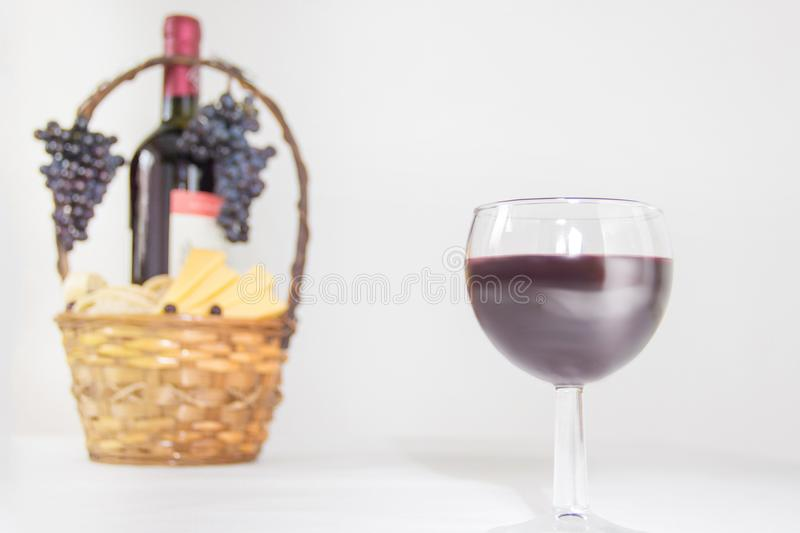 A glass of wine. A bottle of red wine, grapes and picnic basket with cheese slices on white background. stock images