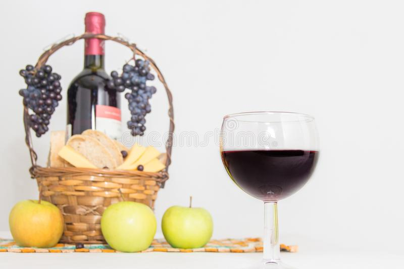 A glass of wine. A bottle of red wine, grapes and picnic basket with cheese and bread slices royalty free stock photos
