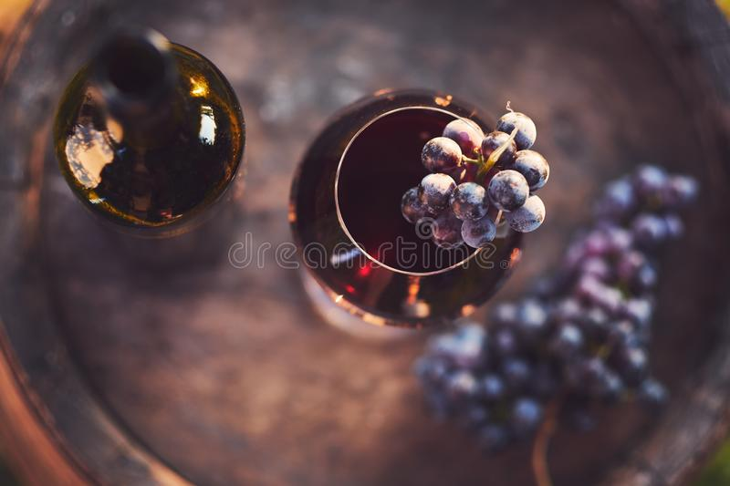 A glass of wine and a bottle of red wine on a wooden barrel royalty free stock photography