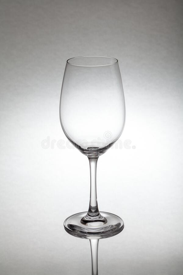 Glass wine glass stands on glass. Close-up of an empty transparent glass wine glass stands on glass on a white background. Below you can see the reflection royalty free stock photos