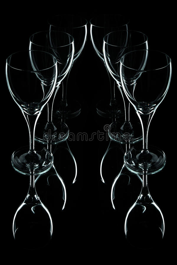 Glass wine glasses on a black background. Six glasses on a black background with reflections royalty free stock photos